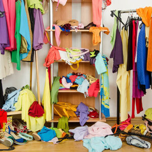 Untidy cluttered woman wardrobe with colorful clothes