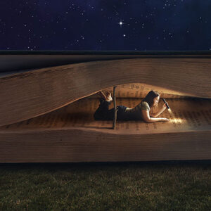 Woman reading inside a huge book at night