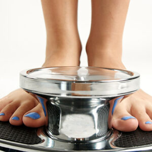 woman's feet with blue toenails on weight scale
